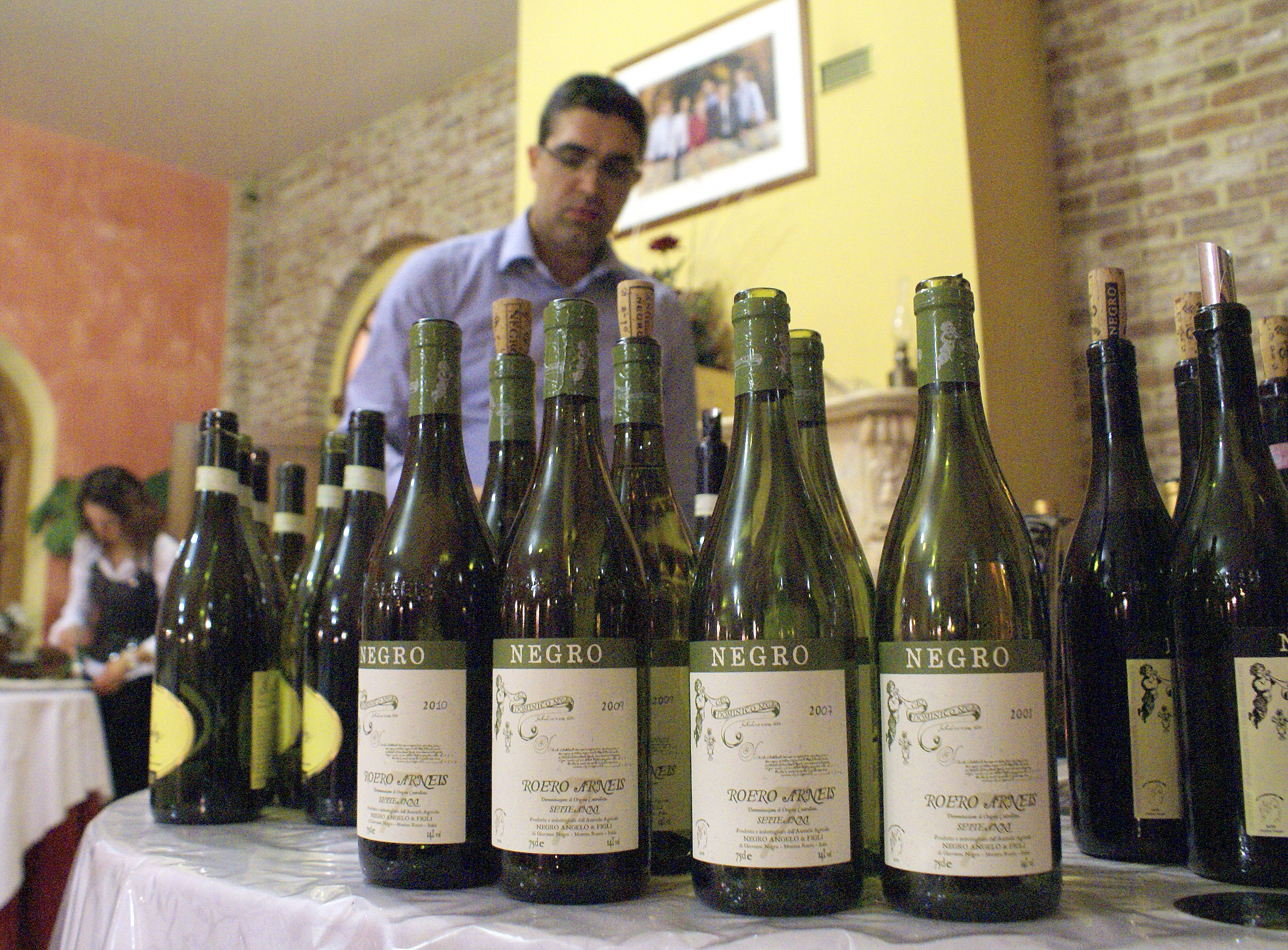 The historical vertical of Negro Arneis; in the background is winemaker Angelo Negro.